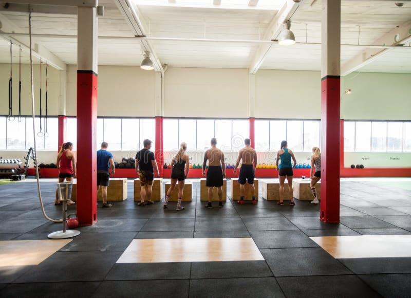 Les hommes et les femmes exécutant la boîte saute dans le studio de forme physique image stock