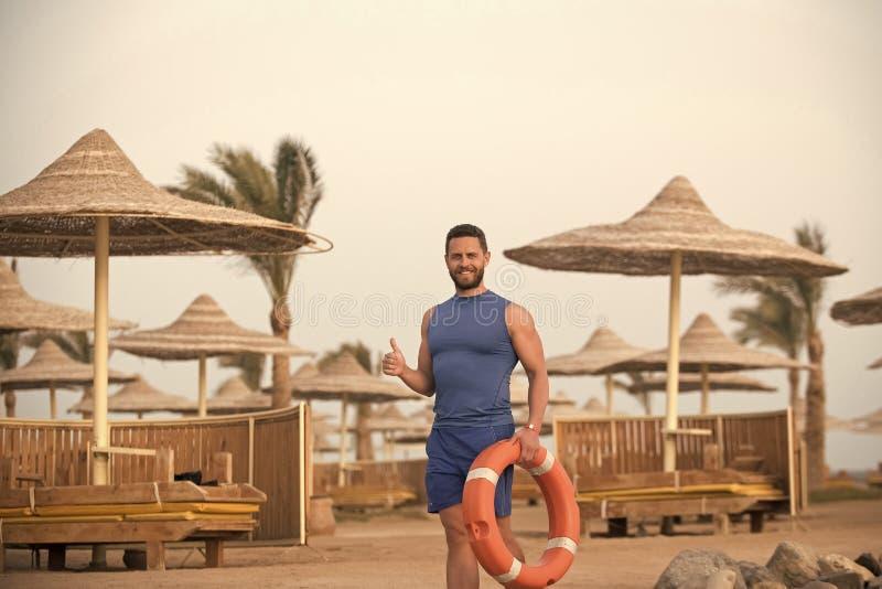 Les hommes guérit le soin de corps Homme avec l'anneau de vie rouge à la plage photo stock