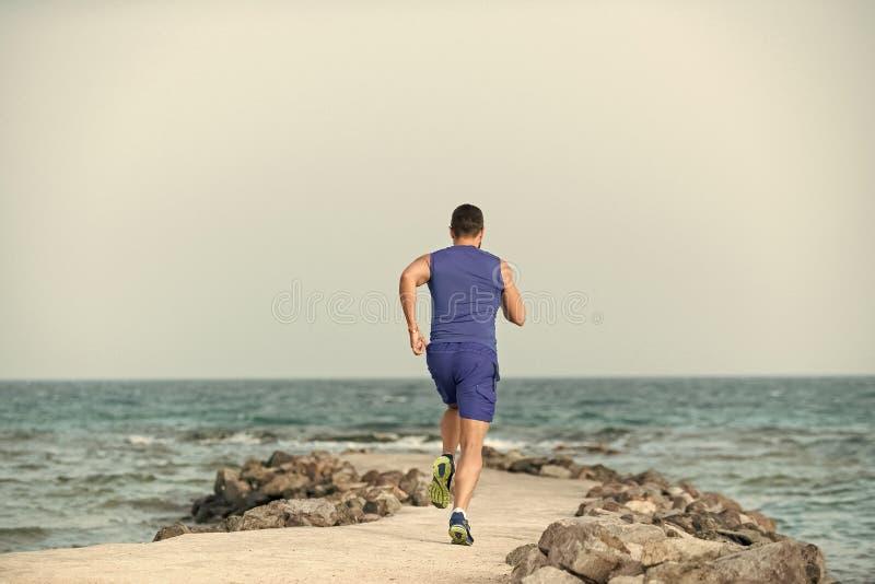 Les hommes guérit le soin de corps Vue arrière de sportif s'exerçant dehors sur le paysage marin photographie stock libre de droits