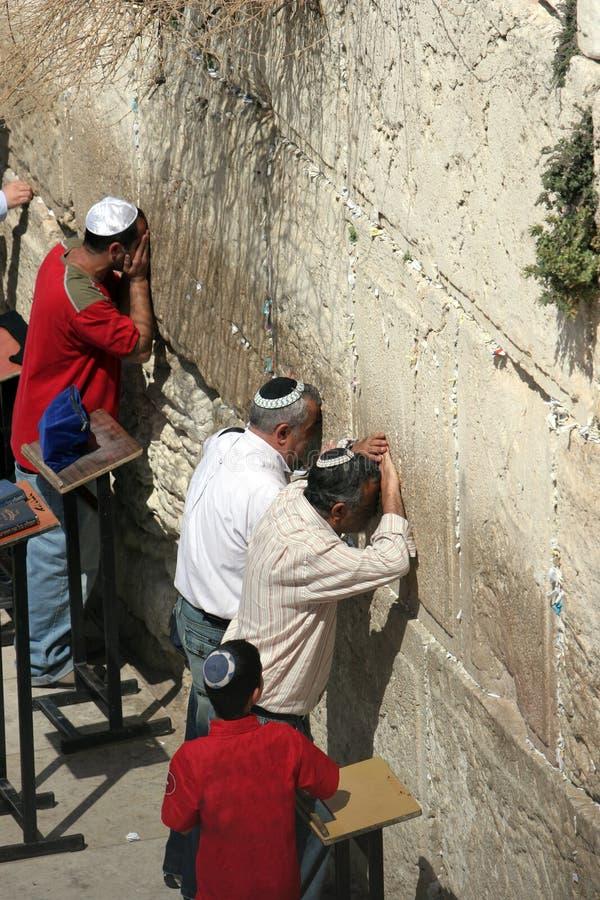 Les hommes juifs prient au mur occidental, observé par un jeune garçon. image stock