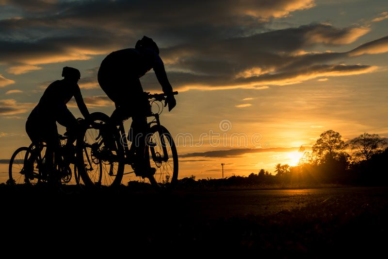 Les hommes montent des vélos au coucher du soleil avec le fond orange-bleu de ciel photo libre de droits