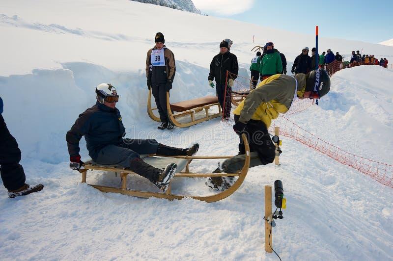 Les hommes montent le klaxon-traîneau traditionnel à la 12ème course annuelle de Klaxon-traîneau d'Alpiglen à Grund dans Grindelw photos libres de droits