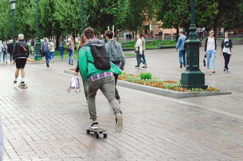 Les hommes montent une planche à roulettes dans Alexander Garden dans la ville de Moscou photographie stock libre de droits
