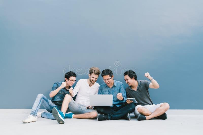 Les hommes multi-ethniques du groupe 4 célèbrent ensemble utilisant l'ordinateur portable Étudiant universitaire, concept d'éduca image stock