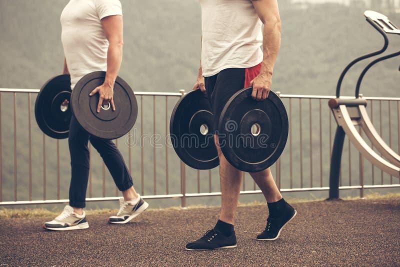 Les hommes musculaires caucasiens avec le poids plaque la préparation à la séance d'entraînement extérieure photos libres de droits