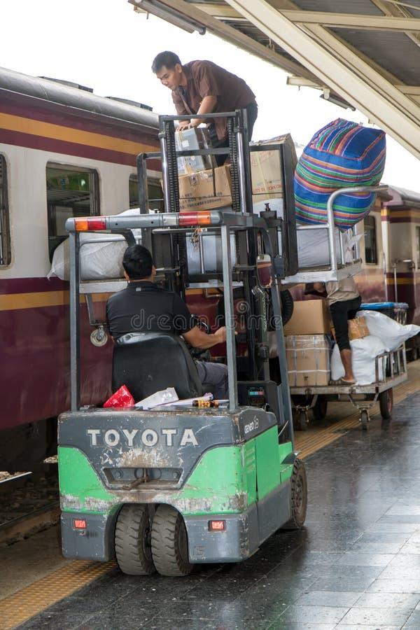 Les hommes ont chargé des paquets dans le train par la fenêtre image stock