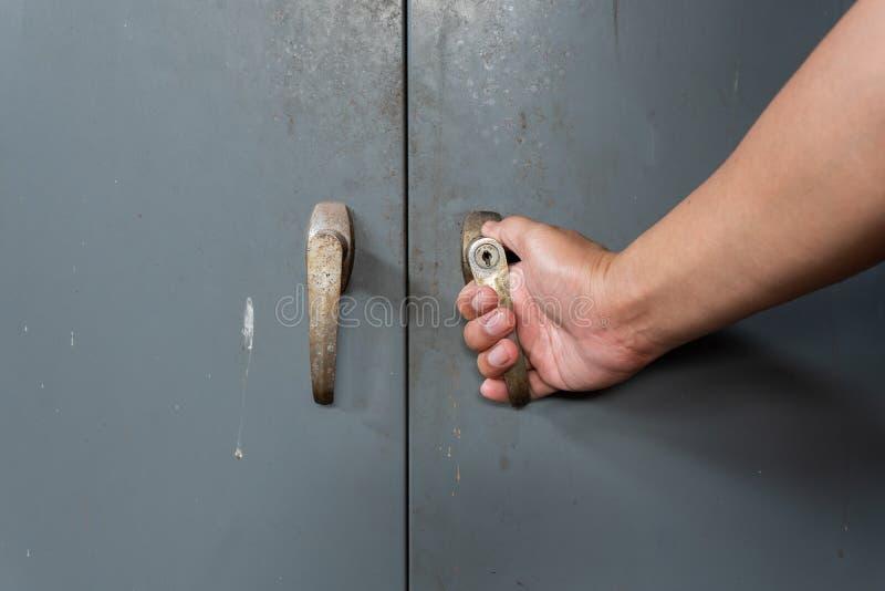 Les hommes ouvre la vieille et rouillée armoire en acier images libres de droits