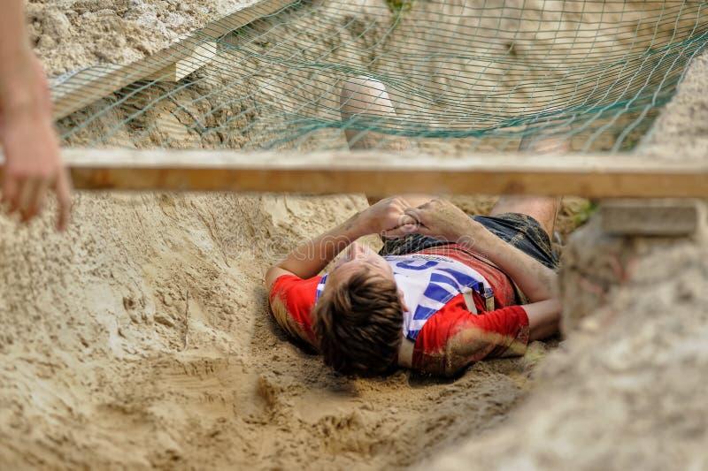 Les hommes rampent sur un retranchement avec de l'eau le sable et images libres de droits
