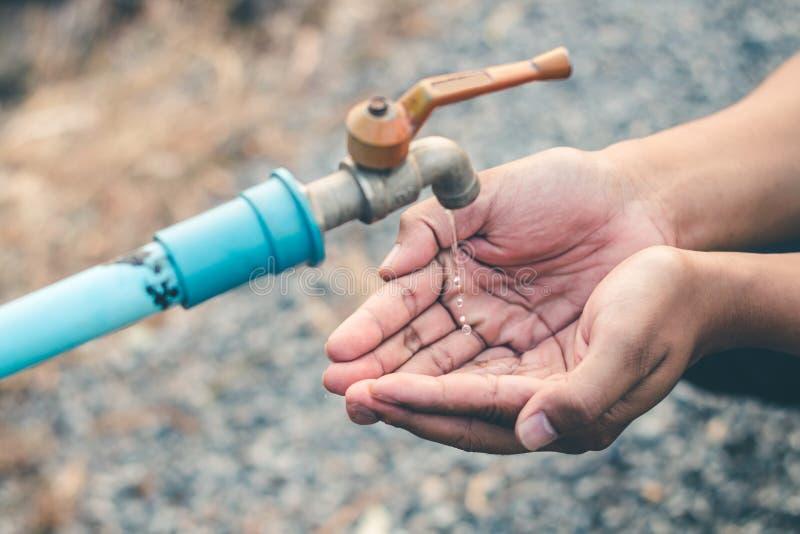 Les hommes remettent attendent pour boire l'eau dans le manque d'eau photo libre de droits