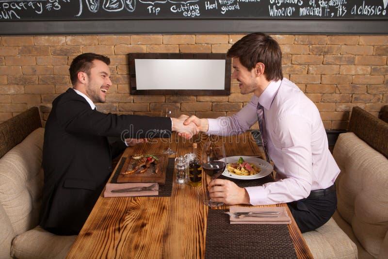Les hommes rient ensemble tout en se reposant en café images stock