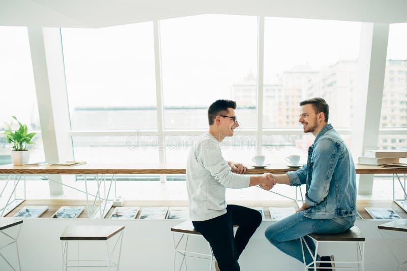 Les hommes s'asseyent à la table en café moderne images stock