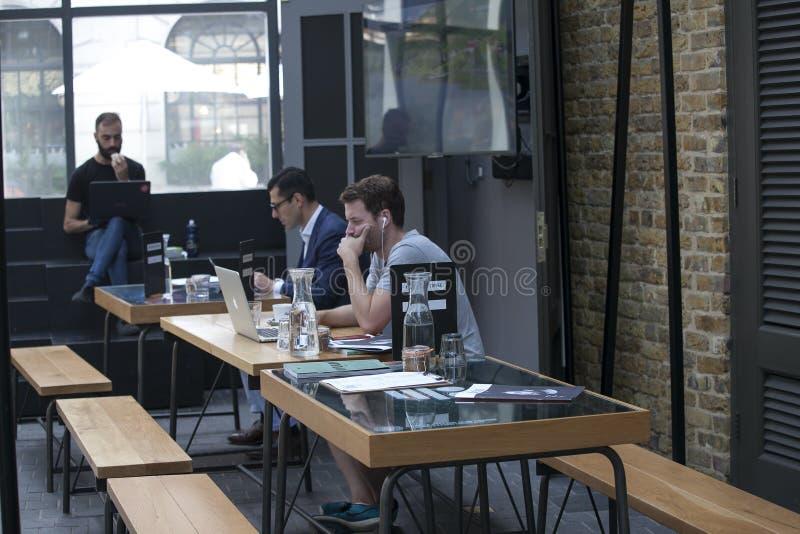 Les hommes s'asseyent aux tables dans un café de rue, boivent du café et lisent des actualités photo stock
