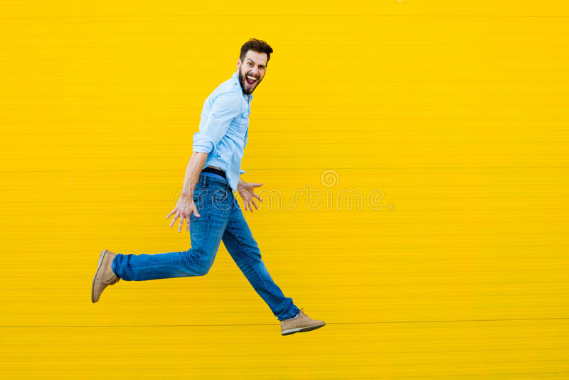 Les hommes sautant sur le fond jaune images stock