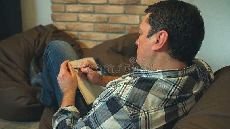Les hommes se reposent sur le sofa et font des notes dans le carnet photos libres de droits