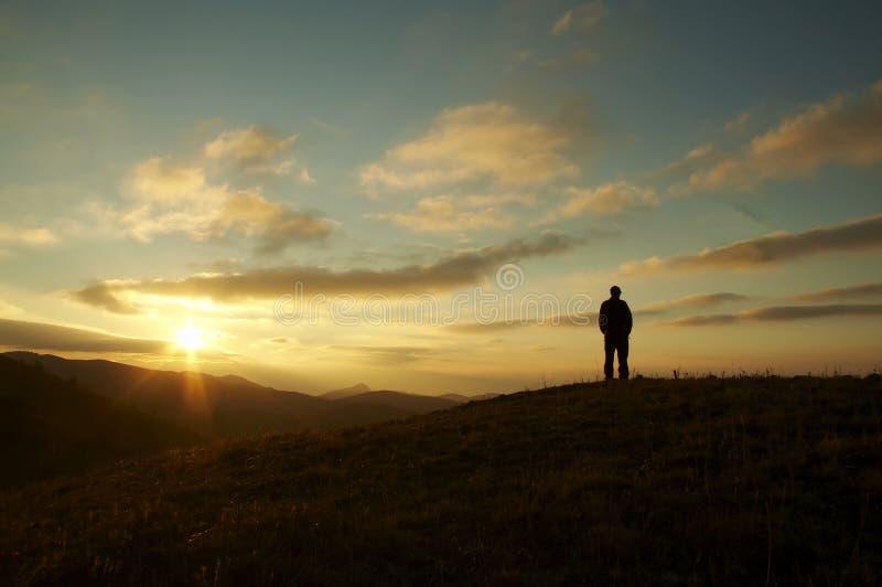 Les hommes silhouettent sur le coucher du soleil images libres de droits