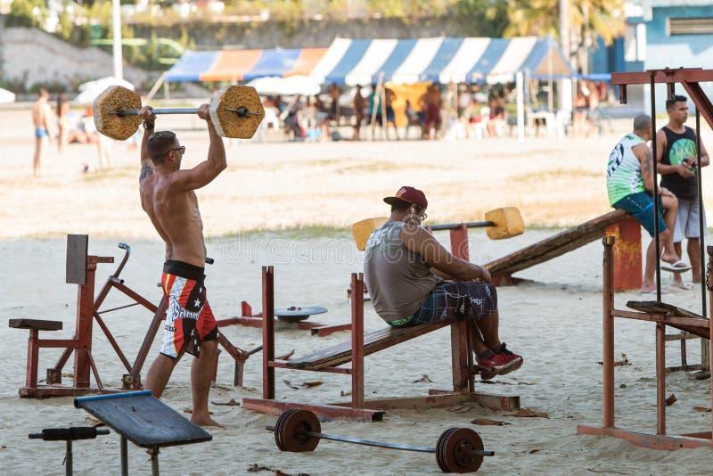 Les hommes soulèvent des poids avec l'équipement brut au gymnase extérieur du Brésil photographie stock libre de droits