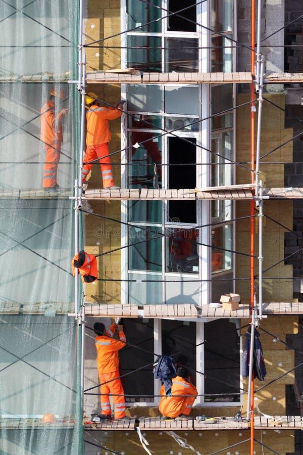 Les hommes travaille à l'échafaudage des constructions photographie stock libre de droits