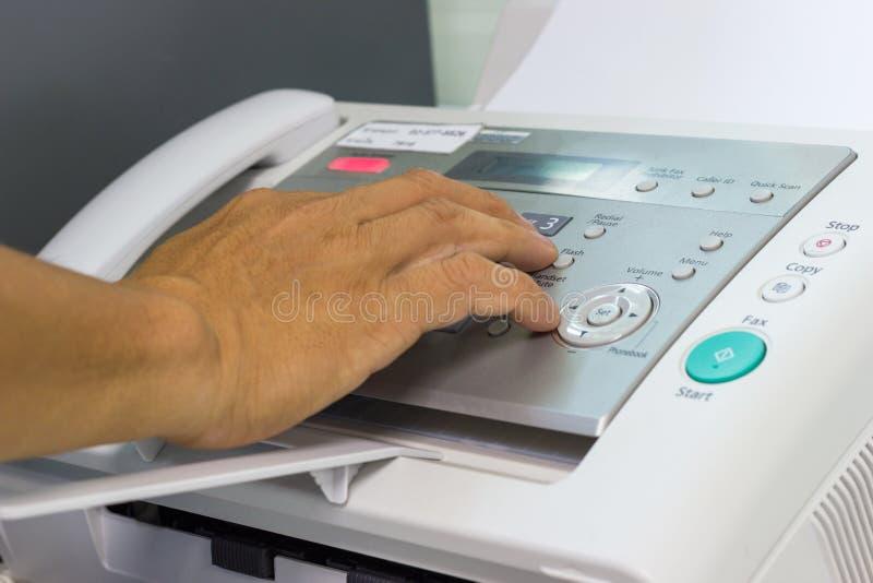 Les hommes utilisent un télécopieur dans le bureau photographie stock