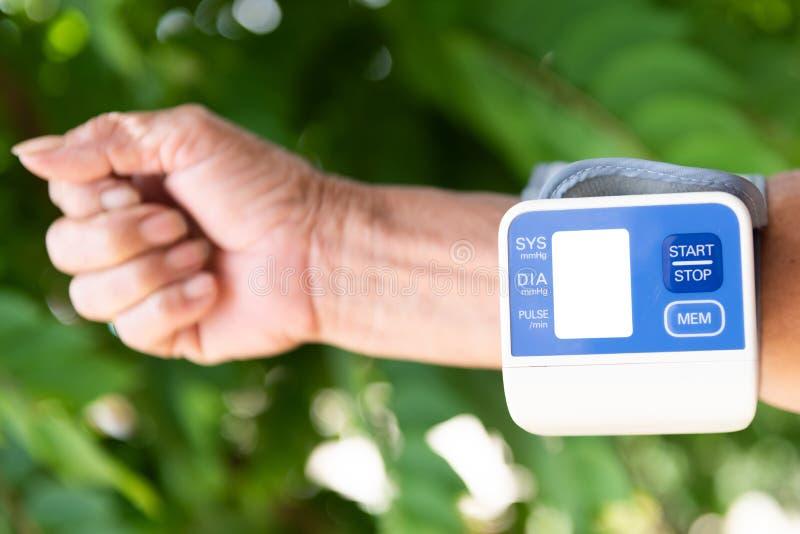 Les hommes vérifient la tension artérielle et la fréquence cardiaque avec l'essai standard numérique de tension artérielle d'indi images libres de droits
