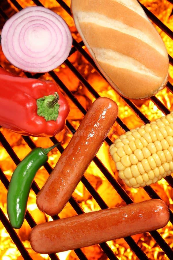 Les hot-dogs, le pain et les veggies sur le barbecue grillent images stock