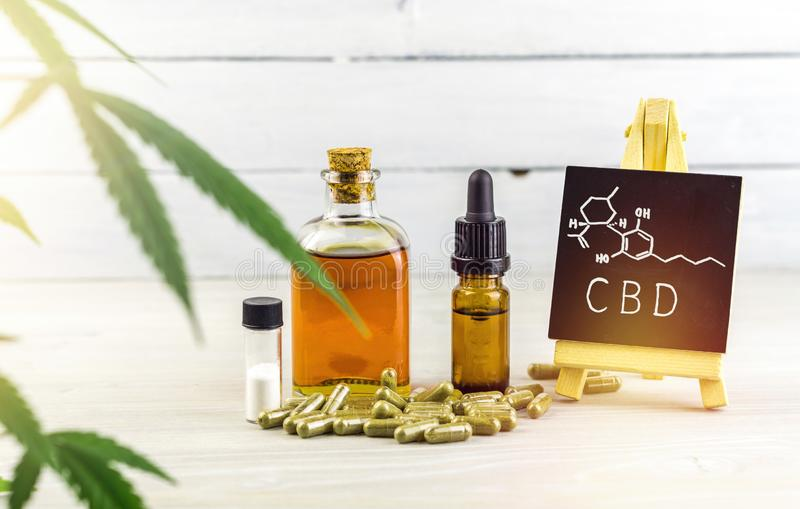 Les huiles, les capsules et les cristaux de Cannabidiol CBD isolent avec le petit tableau noir avec le mot et la constitution chi images stock