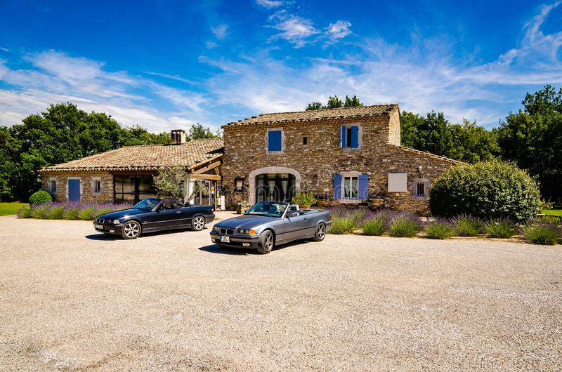 Les Imberts, France - June 16, 2018. Two convertible vintage cars parked in front of typical french provence house. With traditional blue window shutter royalty free stock images