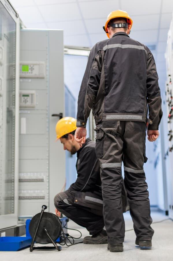 Les ingénieurs de service après-vente inspectent le système avec l'ensemble d'essai de relais équipent image stock