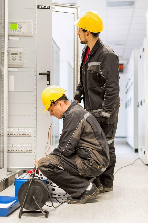 Les ingénieurs de service après-vente inspectent le système avec l'ensemble d'essai de relais équipent images libres de droits