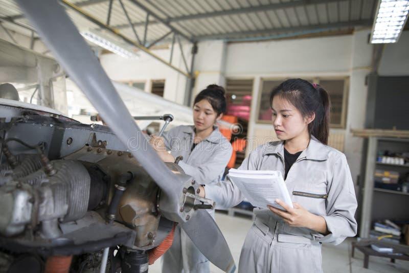 Les ingénieurs et les techniciennes asiatiques de femmes réparent des avions images stock