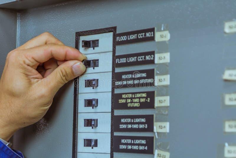 Les ingénieurs masculins sont arrêtent le briseur pour le système électrique de contrôle photographie stock libre de droits