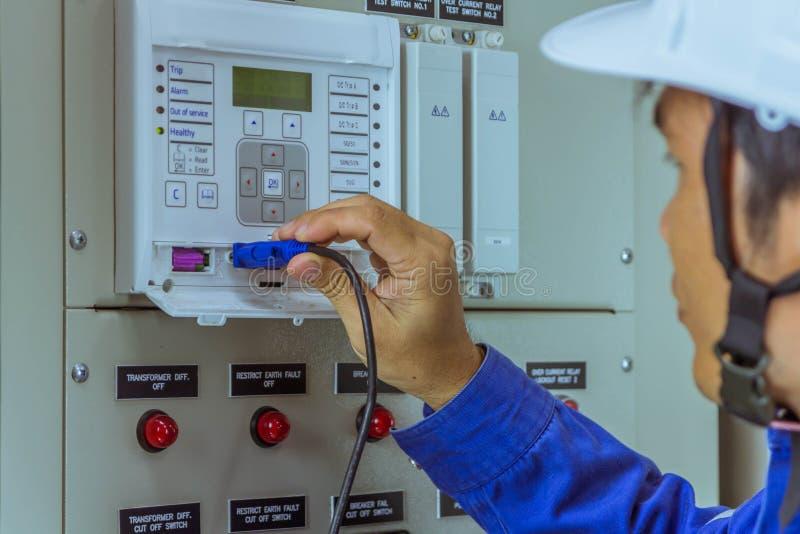 Les ingénieurs masculins sont relient le câble à l'équipement à l'ordinateur portable pour le chec images libres de droits