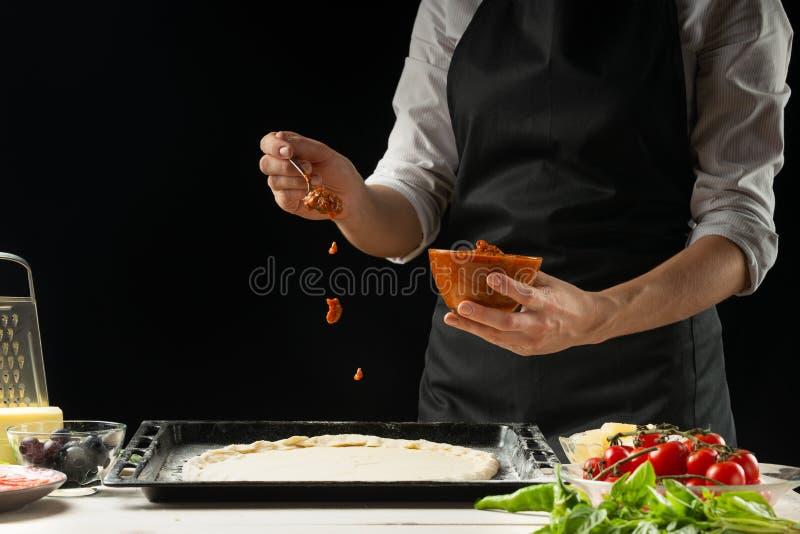 Les ingrédients crus de pizza sur une table en bois, le chef prépare la pizza sur un fond foncé images libres de droits