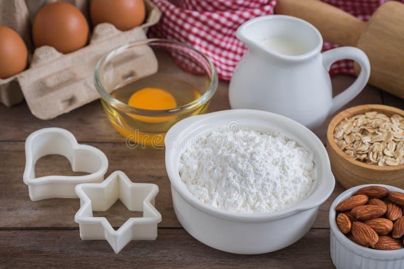Les ingrédients de cuisson flour, egg, traient, les amandes, avoine sur la table photos stock