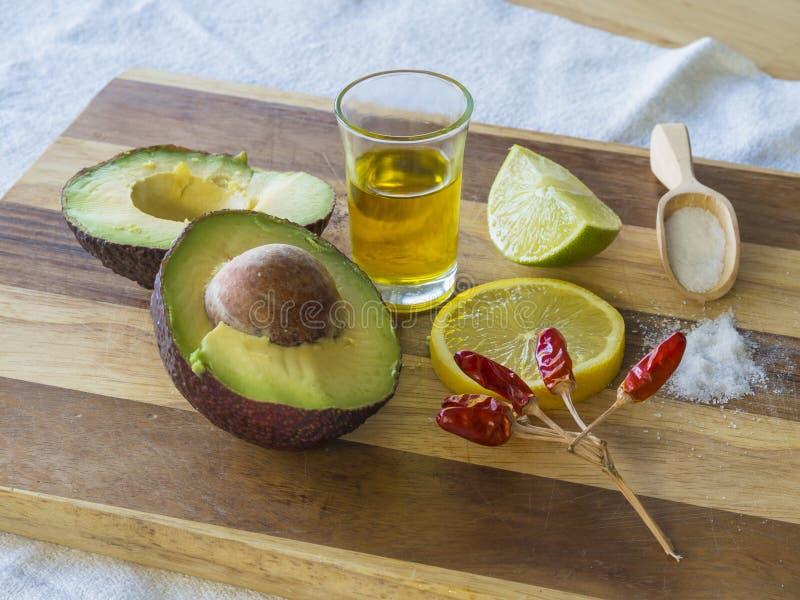 Les ingrédients de guacamole ont divisé en deux le sel mûr de citron de chaux d'avocat courtisent dedans photos libres de droits