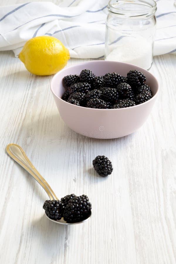Les ingrédients pour des mûres bloquent : baies, citron, sucre sur une surface en bois blanche Plan rapproch? photographie stock libre de droits