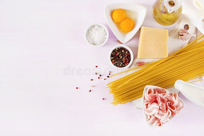 Les ingrédients pour faire cuire les pâtes de Carbonara, spaghetti avec le pancetta, oeuf, poivre image stock
