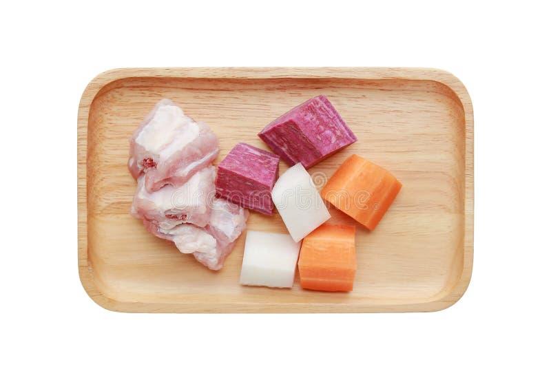 Les ingrédients pour la soupe de ébullition ont coupé la carotte, le radis, l'os de porc et la pomme de terre pourpre dans le pla image stock
