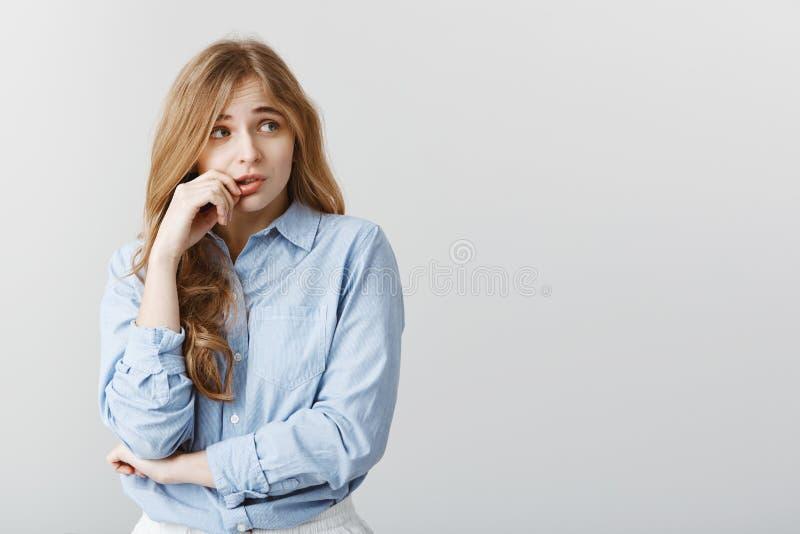 Les inquiétudes de fille quelqu'un connaîtront le secret Tir d'intérieur de femme européenne timide peu sûre dans le chemisier bl photos libres de droits
