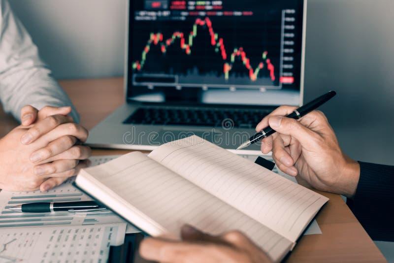 Les investisseurs emploient un stylo à écrire des données pour la société qui analyse les actions avec des collègues au bureau image stock