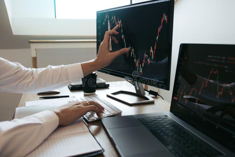 Les investisseurs s'intéressent de près à l'ordinateur portable qui possède des actions d'information sur les investissements et  photographie stock libre de droits