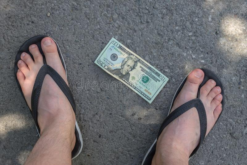 Les jambes d'un adolescent près du billet de banque se trouvant sur l'asphalte images libres de droits