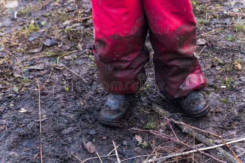 Les jambes d'un enfant dans les combinaisons sales et des chaussures souillées, se tenant au sol image stock