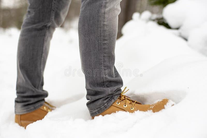 Les jambes d'un homme dans des chaussures jaunes à la mode se tiennent dans une congère, sur un fond brouillé d'un hiver couvert  images libres de droits