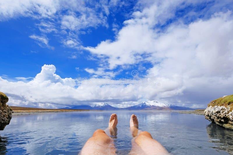 Les jambes d'un homme sportif en source chaude thermale naturelle Polloquere, lac de sel de Salar De Surire, Isluga Volcano Natio photographie stock libre de droits