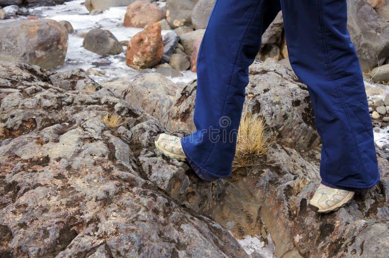 Les jambes d'un randonneur de femme marche au-dessus des roches photos stock