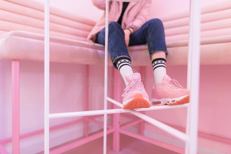 Les jambes d'une fille à la mode dans des espadrilles roses, qui s'assied sur un sofa rose Mode de rue photos stock