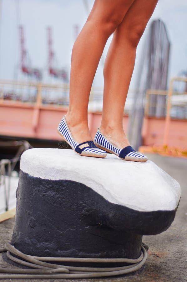 Les jambes dans des chaussures marines de style se tiennent sur la borne dans le port maritime photos stock