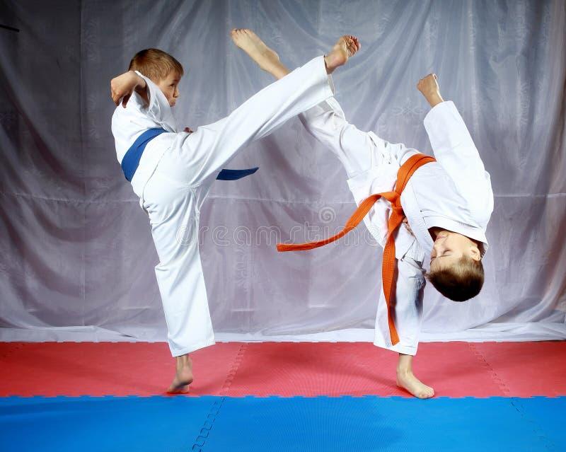 Les jambes de coups pour se rencontrer battent des athlètes dans le karategi image stock