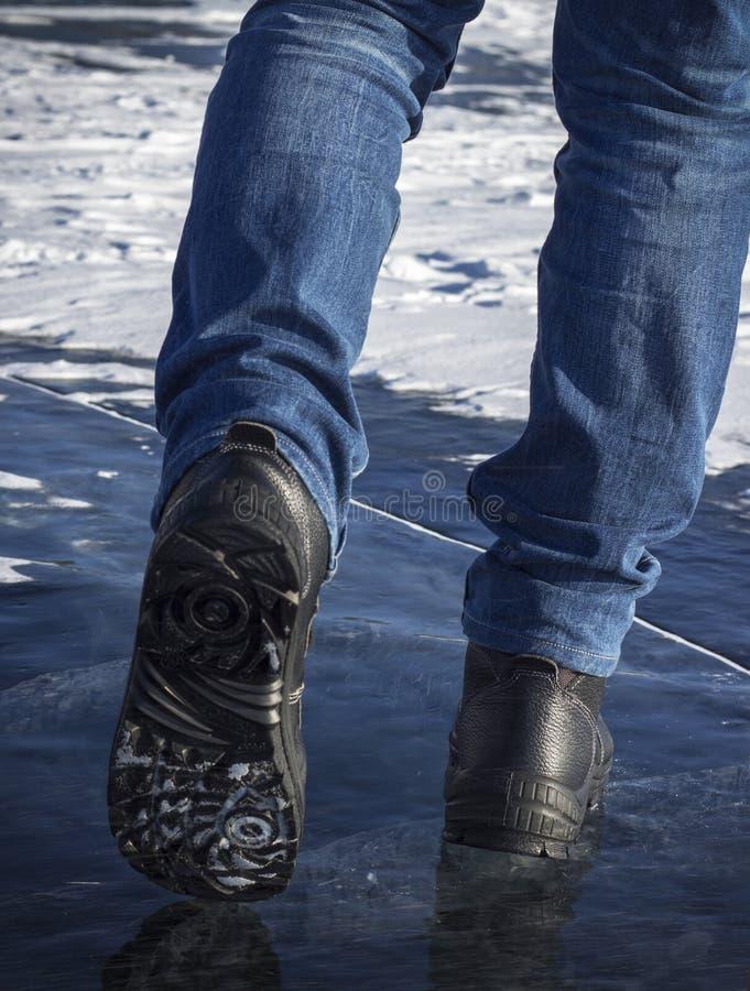 Les jambes de l'homme dans le noir marchant dans la neige photo libre de droits