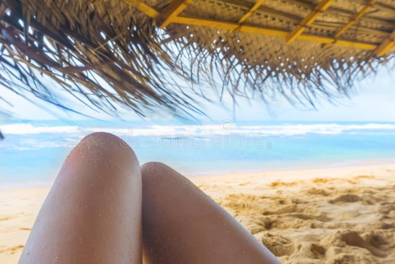 Les jambes de la femme sous le parasol sur la plage tropicale ensoleill photo libre de droits